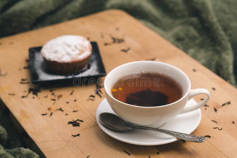 Homemade cupcake with powdered sugar on a black plate and a white cup of tea with natural additives on a wooden tray royalty free stock photography
