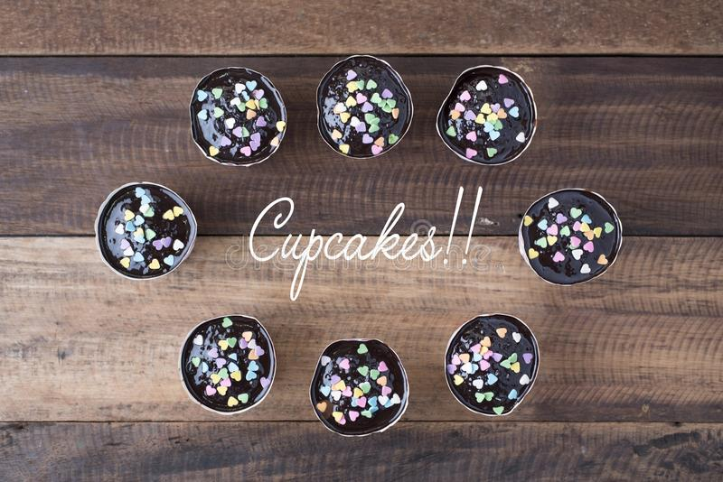 Homemade cupcakes on wooden table top view with `cupcakes!!` word. With lovely sprinkles.cupcakes image for background stock photo