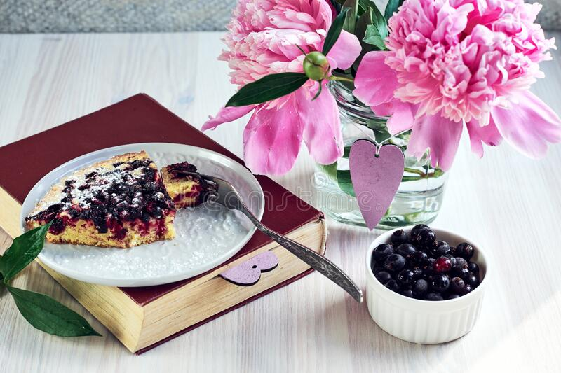 Homemade currant pie. A piece of homemade currant pie in a plate on books and a bouquet of pink peonies, summer day stock image