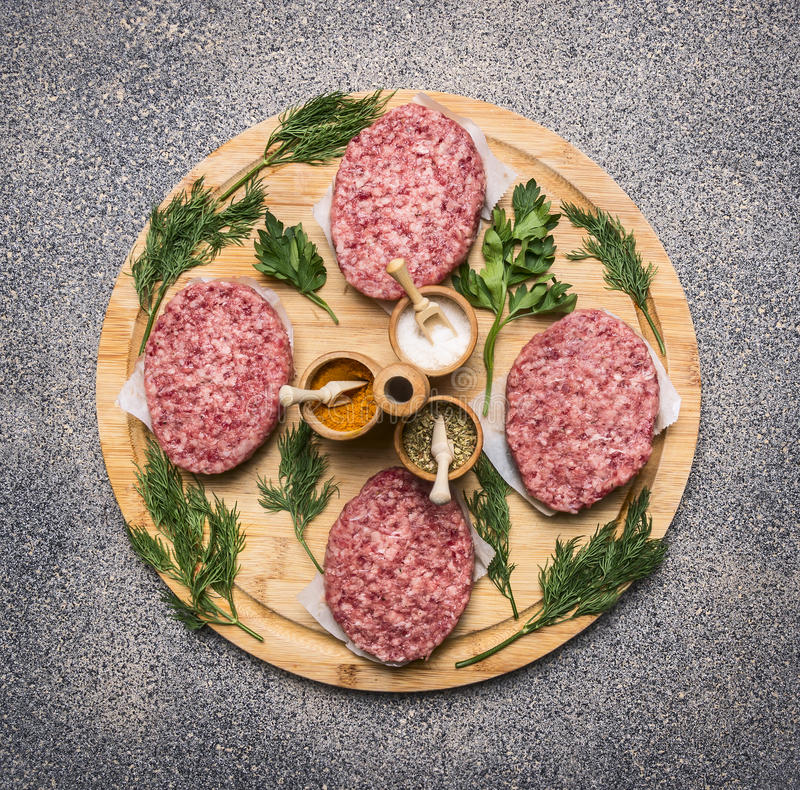 Homemade cutlet of beef for burgers, lined circle on a round wooden chopping board parsley and dill and spices royalty free stock photography