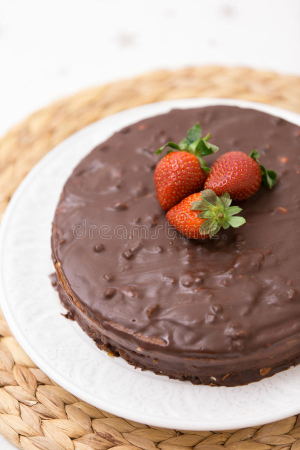 Homemade dark chocolate cake decorated with cocoa and fresh organic strawberries on top served on a white plate and royalty free stock photos