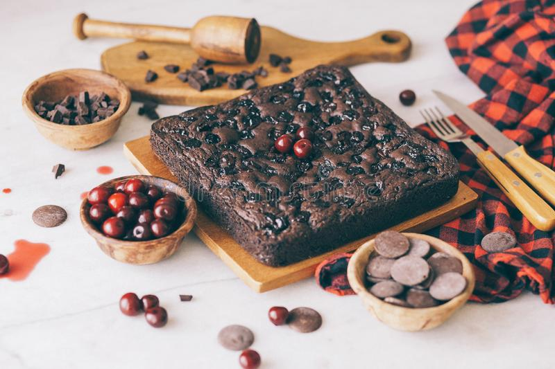 Homemade dark chocolate cherry brownie cake and sweet fresh cherries and delicious chocolate pieces in soft-focus. royalty free stock photography