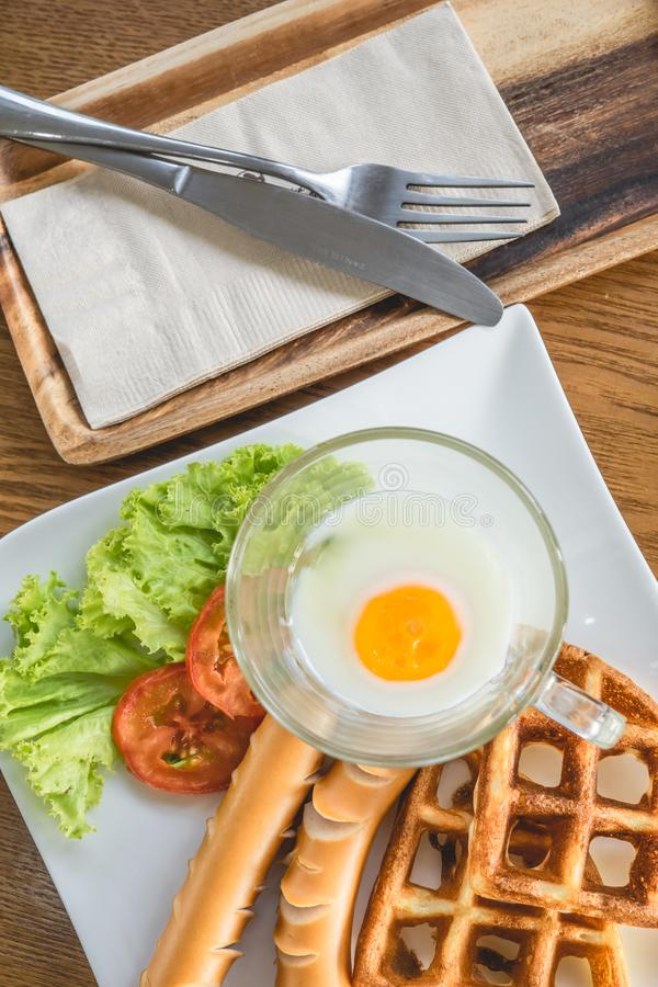 Homemade delicious american breakfast with soft-boiled egg, waffles, sausage, tomato, lettuce on white plate on wood table, top. View background banner closeup stock images