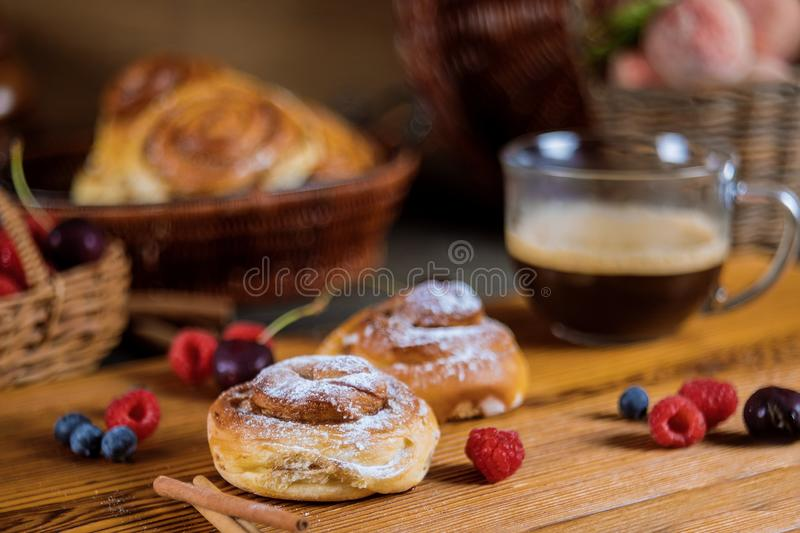 Homemade delicious cinnamon rolls with coffee and cinnamon sticks selective focus. Homemade delicious cinnamon rolls sweet food with coffee and cinnamon sticks royalty free stock photos
