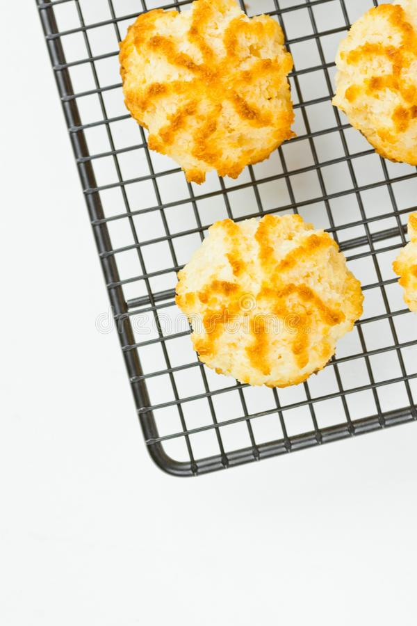 Homemade Delicious Coconut Macaroons Cookies with Golden Crust on Black Metal Cooling Rack White Kitchen Table. Top view royalty free stock image