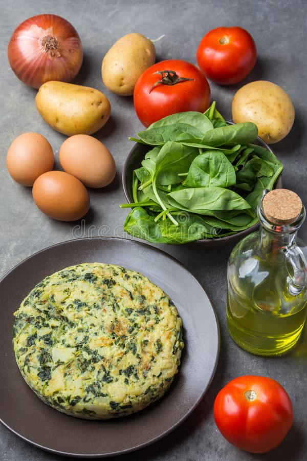 Homemade delicious frittata with spinach on plate. Recipe ingredients potatoes eggs olive oil in bottle tomatoes on dark concrete royalty free stock image
