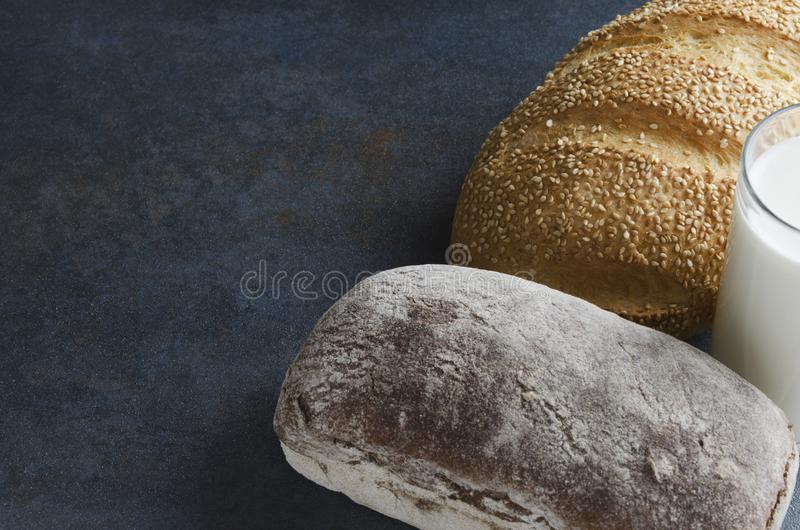 Homemade delicious loaves of bread,glass of milk.Tasty snack time.Rustic mood.Copy space for text royalty free stock photo