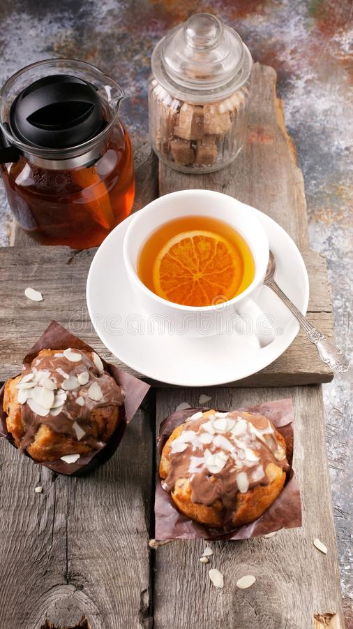 Homemade delicious muffins and fragrant tea on a rustic background. Close-up. Vertical shot royalty free stock photography