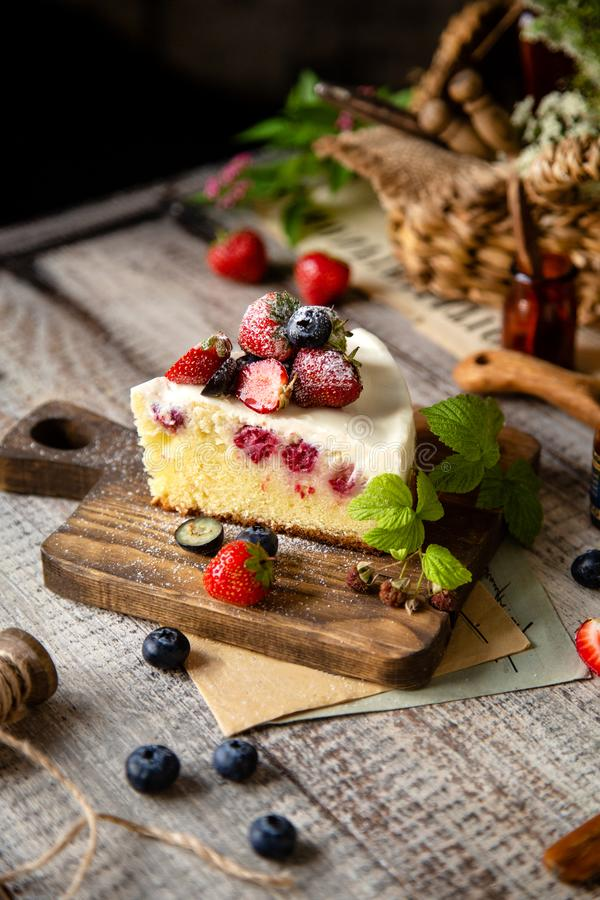 Homemade delicious slice of raspberry biscuit cake with white cream, strawberries, blueberries stock photography