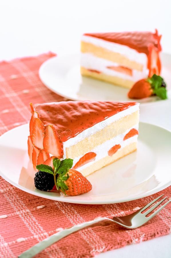 Homemade dessert, two piece of strawberry cake and strawberry jam with fresh raspberry and strawberry on white dishes and table. royalty free stock images
