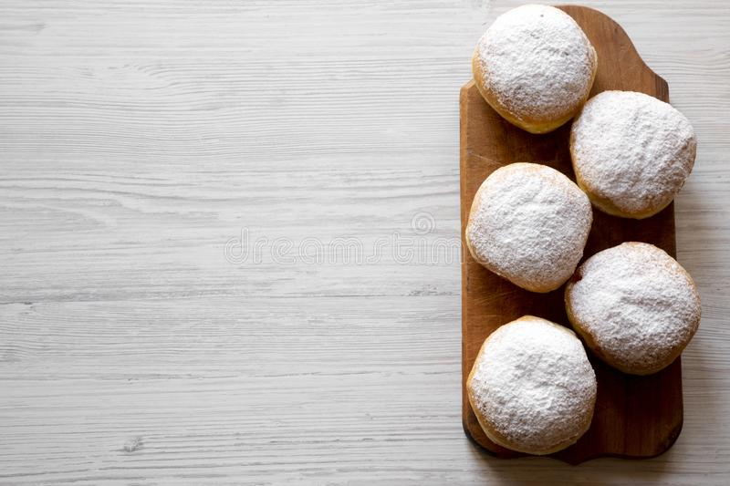Homemade donuts with jelly and powdered sugar on rustic wooden board over white wooden table, top view. Copy space.  stock images