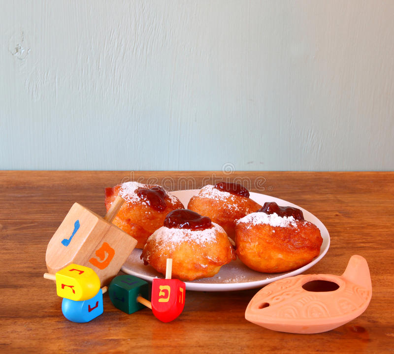 Homemade donuts and wooden dreidels (spinning top) for hanukkah jewish holiday over wooden table stock image
