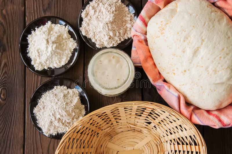 Homemade dough, sourdough in a jar, mix of flours, bread and basket for proof and spatula on a wooden background. Baking concept. stock photos