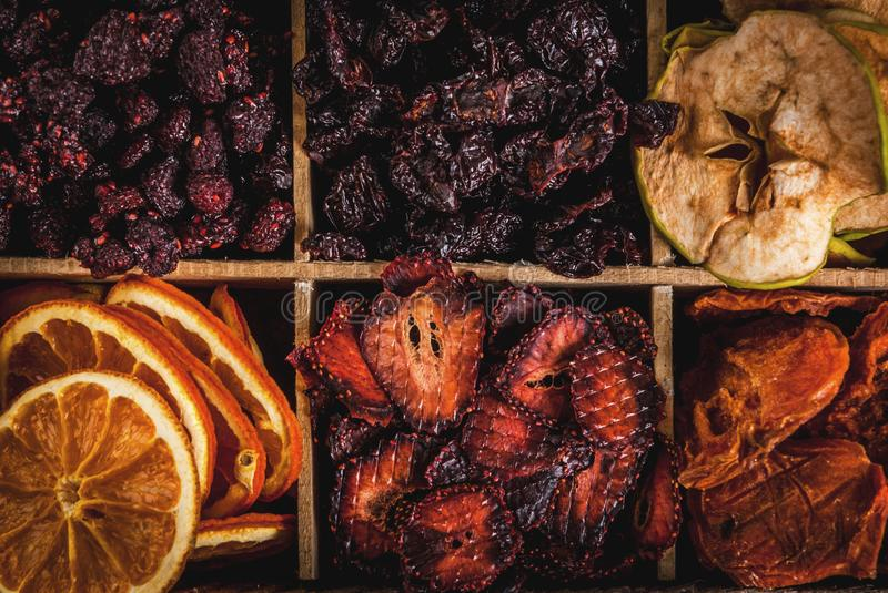 Homemade dried berries and fruits. Harvest for the winter: apricots, apples, strawberries, raspberries, cherries, oranges. In old wooden box, on black stone stock photography