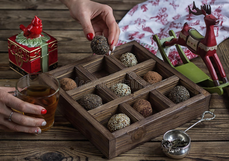Homemade dried fruits and nuts candy balls. With cocoa powder, sesame and chia seeds on rustic wooden background. Healthy Eating concept. Selective focus royalty free stock photos