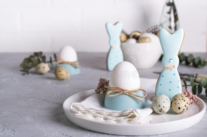 Homemade easter cookies in the shape of a funny bunny, quail eggs and chicken egg. Easter celebration table setting. Holiday decorations royalty free stock photo