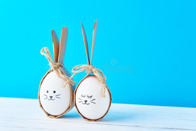 Homemade easter eggs with faces and rabbit ears on a blue background royalty free stock photography
