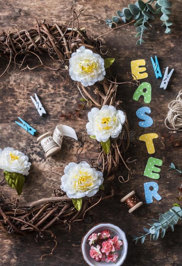 Homemade Easter wreath of vines with flowers, paper letters, ribbons on a wooden background, top view. Easter craft decorations ho. Me. Concept of creativity royalty free stock images
