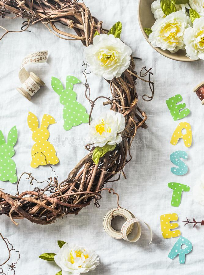 Homemade Easter wreath of vines with flowers, paper rabbits, ribbons on a white background, top view. Easter craft decorations hom. E. Concept of creativity royalty free stock image