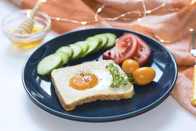 Homemade egg in a hole with toast bread and vegetables on a blue ceramic plate with honey on a white background, close up, indoor. Homemade egg in a hole with stock photos