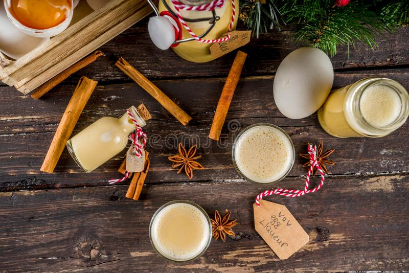 Homemade egg liquor. Traditional Italian Vov eggs liquor. German Egg Liqueur Eierlikor. In different bottle and shot glasses, Wooden background copy space with stock image