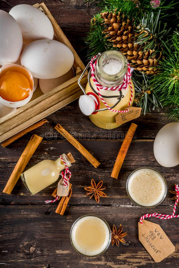 Homemade egg liquor. Traditional Italian Vov eggs liquor. German Egg Liqueur Eierlikor. In different bottle and shot glasses, Wooden background copy space with royalty free stock images