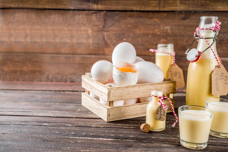 Homemade egg liquor. Traditional Italian Vov eggs liquor. German Egg Liqueur Eierlikor. In different bottle and shot glasses, Wooden background copy space royalty free stock photography