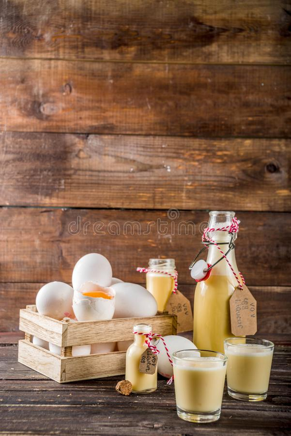 Homemade egg liquor. Traditional Italian Vov eggs liquor. German Egg Liqueur Eierlikor. In different bottle and shot glasses, Wooden background copy space royalty free stock image
