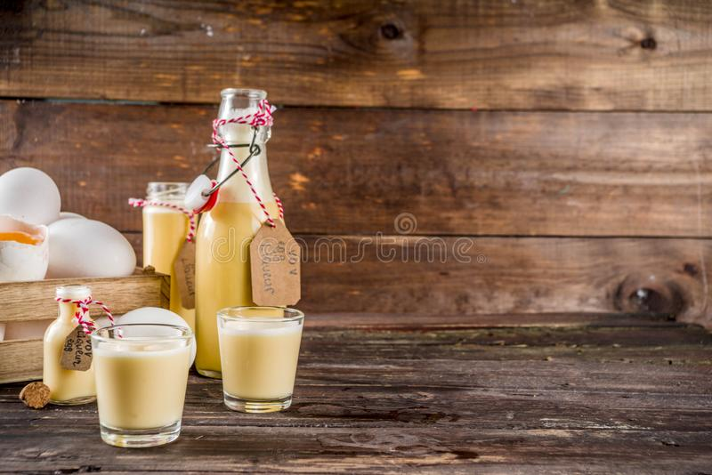 Homemade egg liquor. Traditional Italian Vov eggs liquor. German Egg Liqueur Eierlikor. In different bottle and shot glasses, Wooden background copy space stock photography