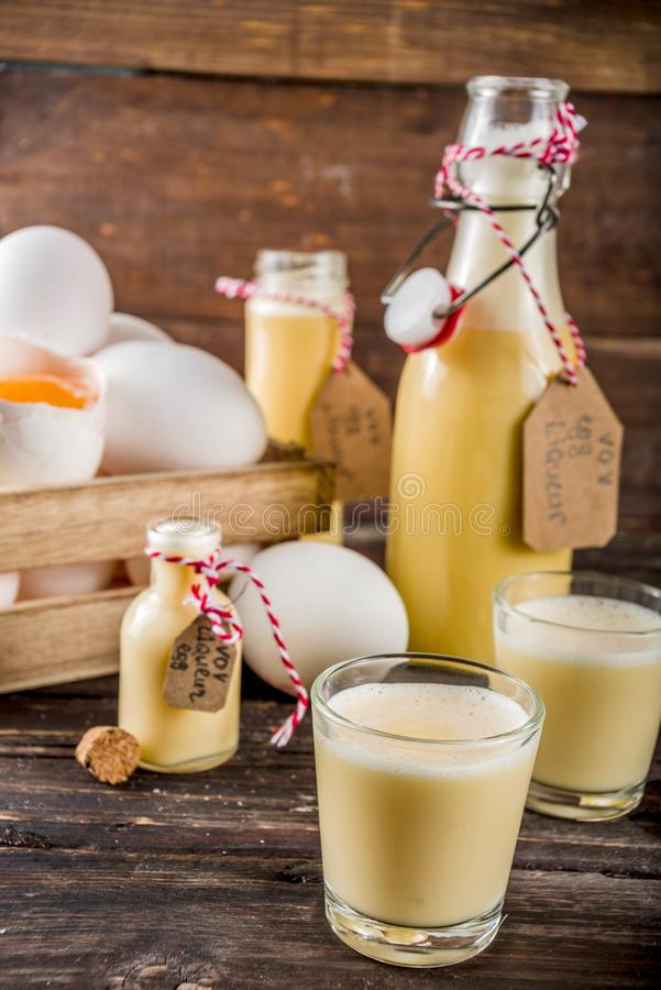 Homemade egg liquor. Traditional Italian Vov eggs liquor. German Egg Liqueur Eierlikor. In different bottle and shot glasses, Wooden background copy space royalty free stock photo