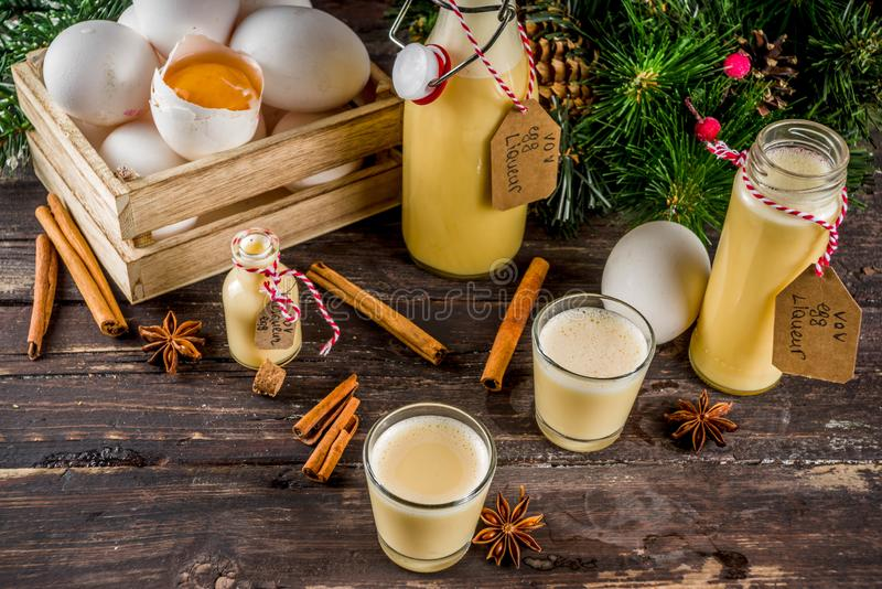 Homemade egg liquor. Traditional Italian Vov eggs liquor. German Egg Liqueur Eierlikor. In different bottle and shot glasses, Wooden background copy space with royalty free stock photography