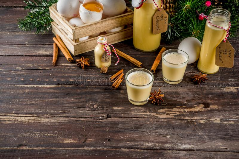 Homemade egg liquor. Traditional Italian Vov eggs liquor. German Egg Liqueur Eierlikor. In different bottle and shot glasses, Wooden background copy space with royalty free stock image