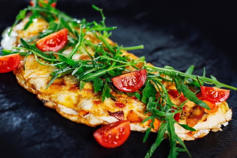 Homemade egg omelette for breakfast. omelette garnished with tomato and green fresh rucola salad. Homemade egg omelette for breakfast. omelette garnished with royalty free stock photo