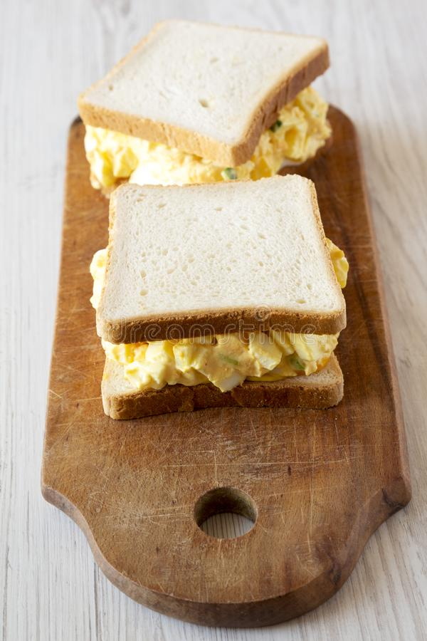 Homemade egg sandwich for breakfast over white wooden surface, low angle view. Close-up royalty free stock images