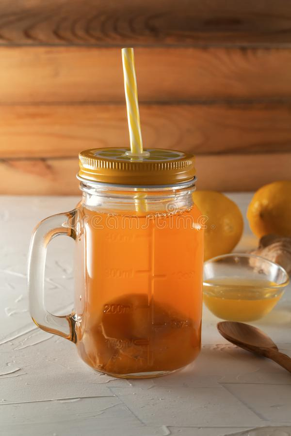 Homemade fermented drink Kombucha in glass jar with lemon, honey and ginger on a wooden table. stock image