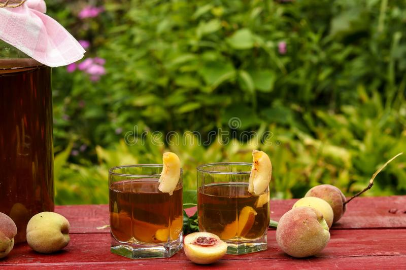 Fermented Raw Kombucha Tea with Peach, Summer Healthy Detox Drink in jar and two glass, Horizontal Orientation. Homemade Fermented Raw Kombucha Tea with Peach royalty free stock images