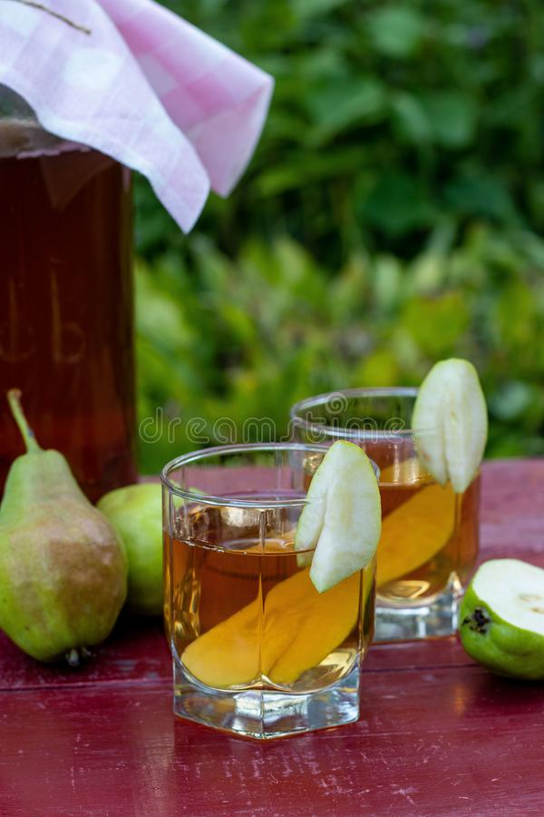 Fermented Raw Kombucha Tea with Pears, Summer Healthy Detox Drink in jar and two glass, vertical orientation. Homemade Fermented Raw Kombucha Tea with Pears stock photography
