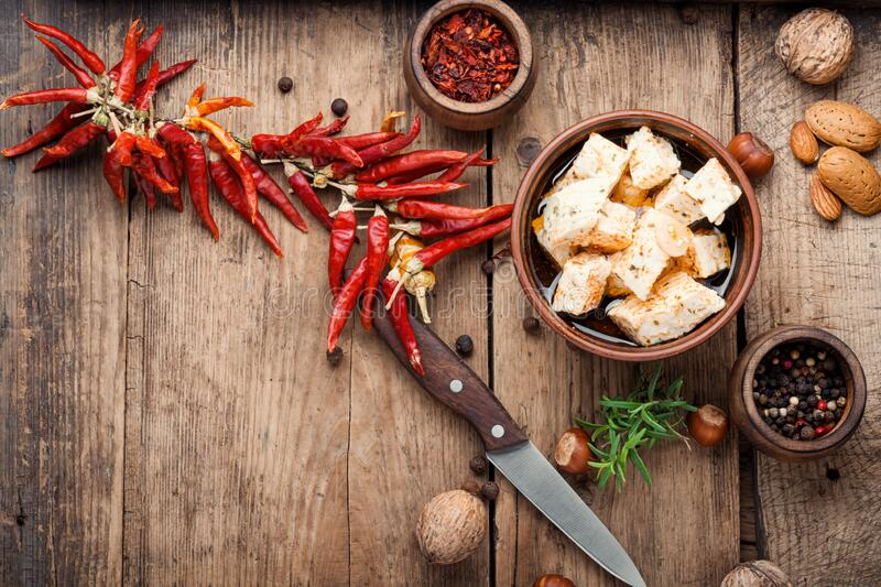 Homemade feta cheese with herbs. Feta cheese with spice and garlic on old wooden background royalty free stock photo