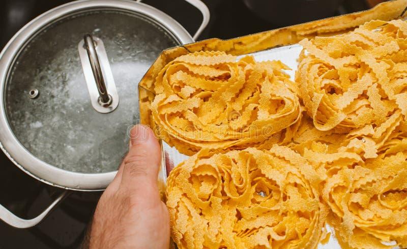 Man preparing to boil italian egg pasta stock image
