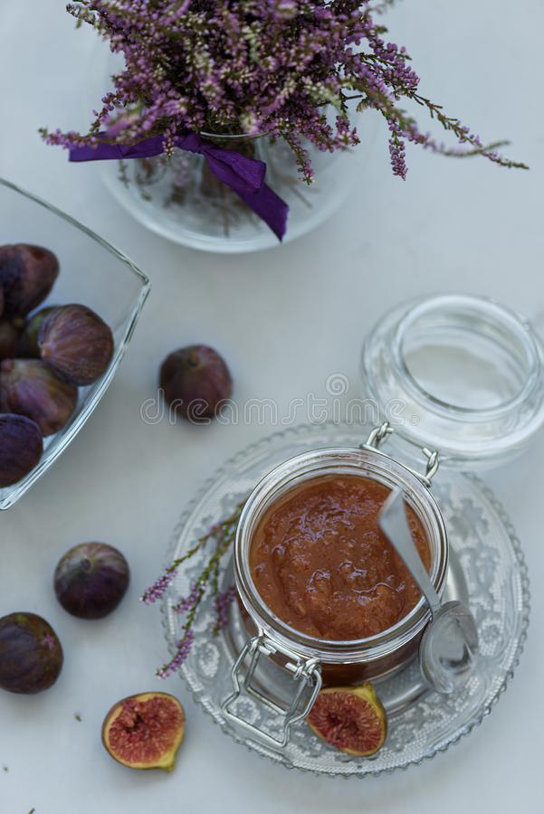 Homemade fig jam in glass jar with fresh purple figs on gray wooden background. Soft focus. Harvesting time or healthy food royalty free stock photography