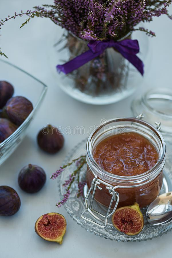 Homemade fig jam in glass jar with fresh purple figs on gray wooden background. Soft focus. Harvesting time or healthy food. Concept stock image