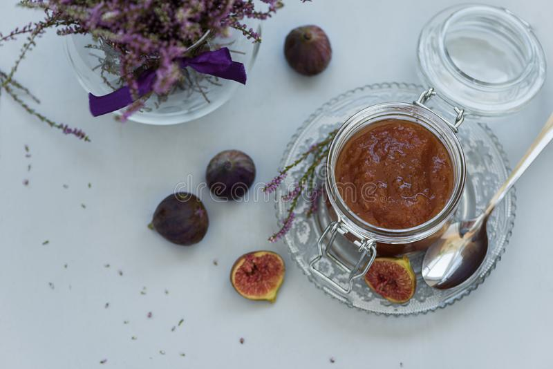 Homemade fig jam in glass jar with fresh purple figs on gray wooden background. Soft focus. Harvesting time or healthy food. Concept. Top view royalty free stock photography