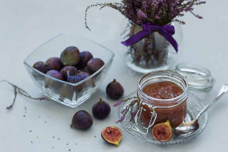 Homemade fig jam in glass jar with fresh purple figs on gray wooden background. Soft focus. Harvesting time or healthy food. Concept stock images