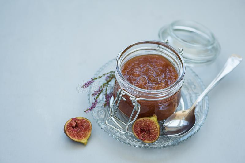 Homemade fig jam in glass jar with fresh purple figs on gray wooden background. Soft focus. Harvesting time or healthy food. Concept royalty free stock photography