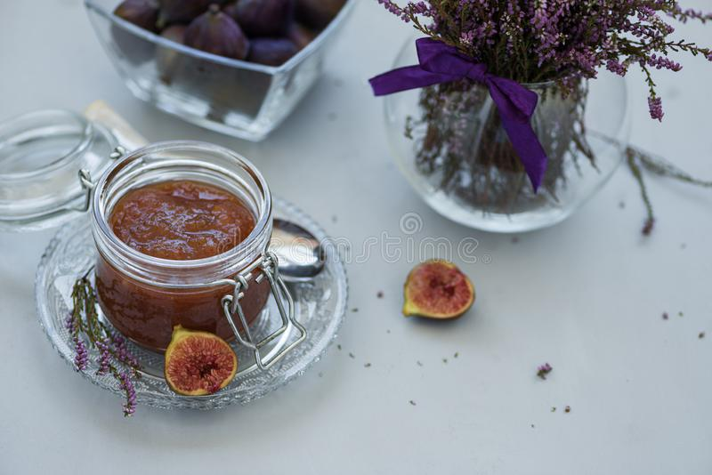 Homemade fig jam in glass jar with fresh purple figs on gray wooden background. Soft focus. Harvesting time or healthy food. Concept royalty free stock images