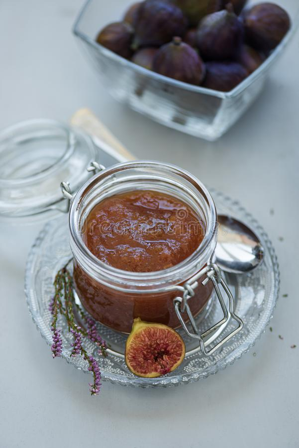Homemade fig jam in glass jar with fresh purple figs on gray wooden background. Soft focus. Harvesting time or healthy food royalty free stock images