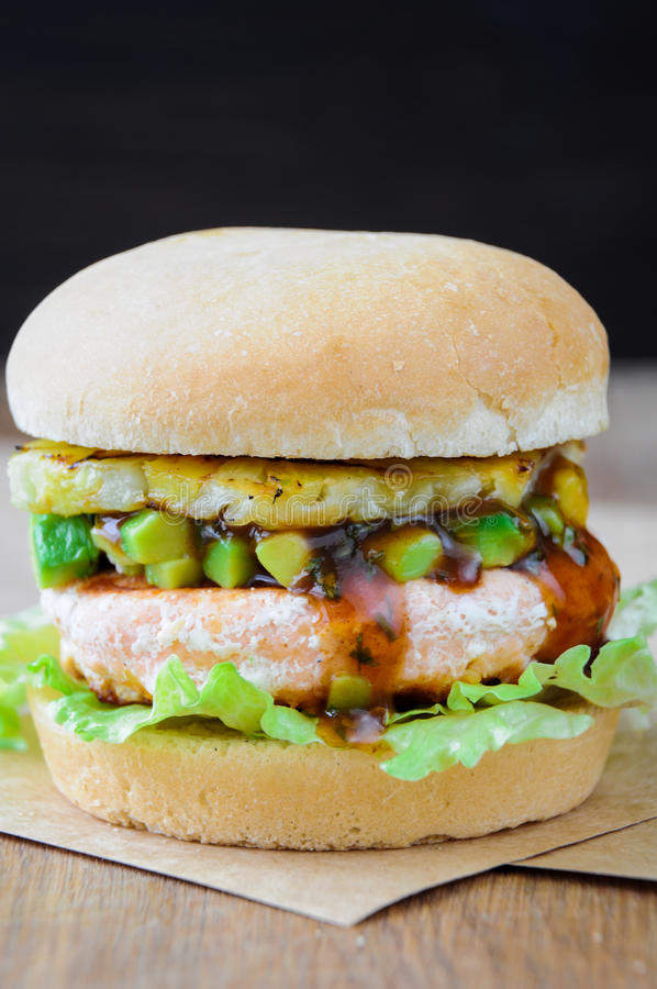 Homemade fish burger with salmon, avocado and pineapple.Close up stock image