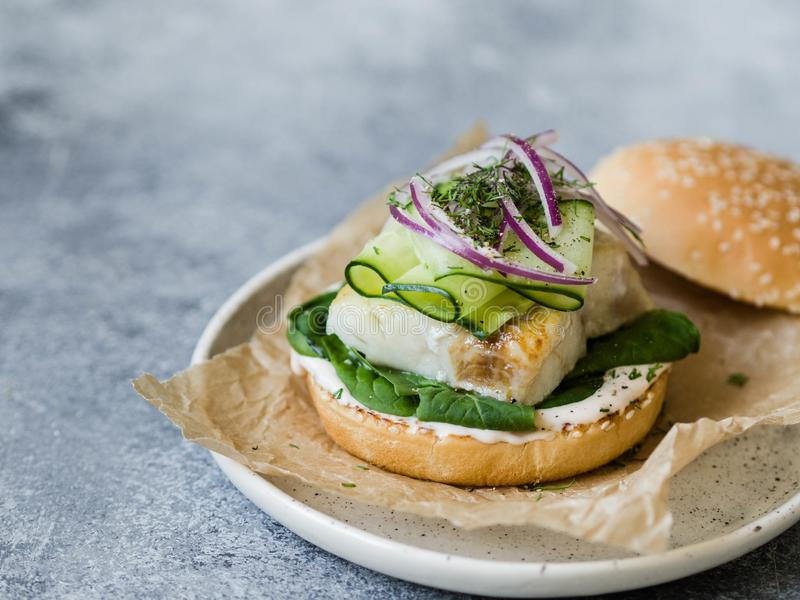 Homemade fish burger of white fish fillet with cucumber slice, red onion, fresh dill and spinach on a white plate stock image