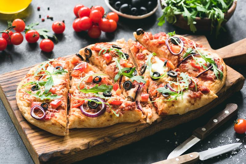 Homemade flatbread pizza garnished with fresh arugula royalty free stock photos