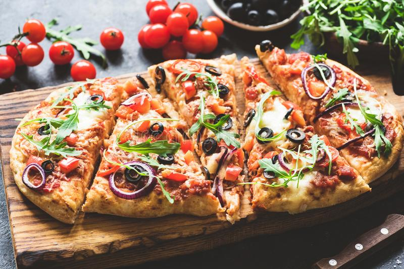 Homemade flatbread pizza sliced on wooden cutting board royalty free stock images